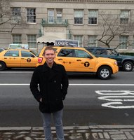 In this photo Stephen is in front of one of his advertisements that is on top of a cab in NYC.
