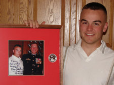 Kevin Fallon displaying photo of himself with the Commandant (the highest ranking officer in the Marine Corps).