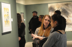 Two young women talk at a Handwerker Gallery reception