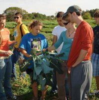 students gatherered in discussion at Sticks n Stones Farm