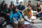 Tabla artists sitting by their drums with violinist