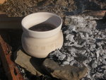 A white ceramic vessel with surface decoration in an open campfire.