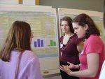 Jenn Rodgers and Jolie Baumann explain a poster