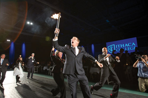 President Tom Rochon carries the torch to the stage