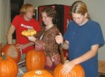 students carving pumpkins as part of a Sustainable holiday activity
