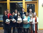 A picture of students holding tabla or percussive instruments they have larned to play