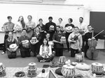Students posing for a photo holding tabla drums