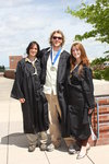 Three smiling students in commencement robes standing on sunny terrace