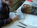 Student refining a drawing based on observation through miscroscope