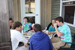 students in colorful teeshirts eating at outside table