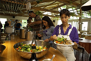 An EcoVillage resident prepares a salad at the weekly community dinner.