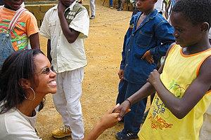 Associate professor Henderson greeting children on her trip to Africa.