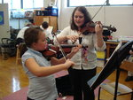 student teaching student how to play violine