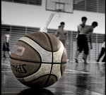 A basketball lay unused as players in the background moveabout the floor.