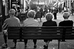 Two elderly couples share a bench to watch the festivites in Certaldo, Italy.
