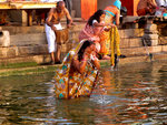 A woman washes her face with the waters of the Ganges while people in the background wash clothes.
