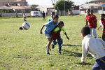 Children play soccer on a grassy field in Cape Town, South Africa.