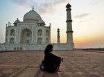A woman sits alone in the vast plaza outside the Taj Mahal, watching as the sun sinks toward the distant horizon.