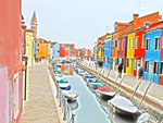 Small watercraft line a canal that runs through a section of vibrantly colored houses in Burano, Italy.