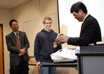 Ithaca College student Jordan Rosas (center) presents professor ao Qin with a thank you gift.