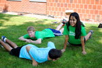 Two freshman and a junior lay on the ground playing an icebreaker game.