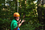 A girl hold up her hands as she glides by on a zip line.