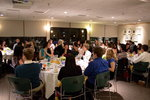 Students and faculty applaud while sitting around dinner tables.