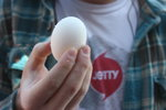 person in plaid shirt holding whole egg