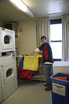 A student utilizes the drying racks in the laundry room