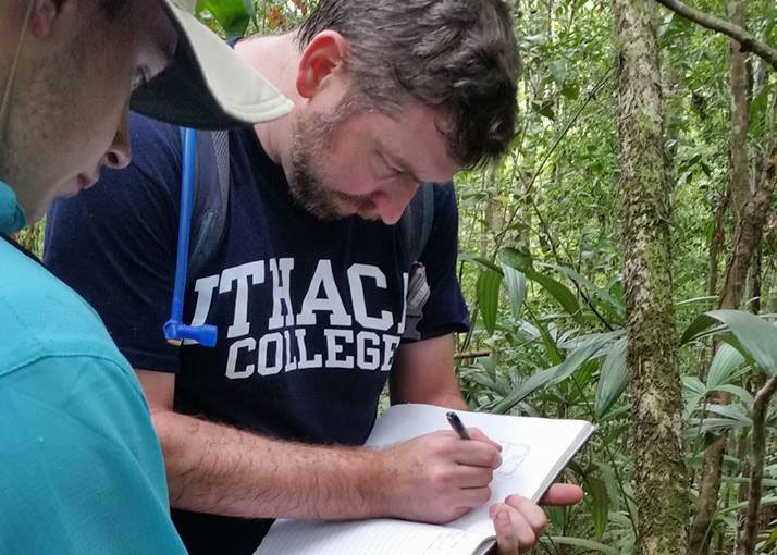 Thomas Garrison jots field notes in the jungles of Guatemala