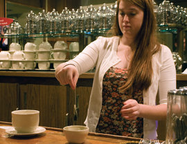 A barista prepares tea in the tc lounge.