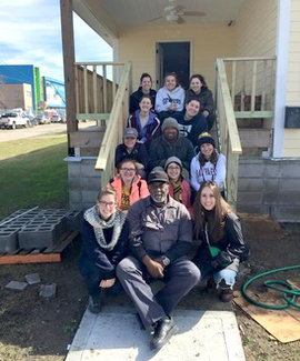 A group of Park scholars sit with local residents on the steps of a home they were helping to restore in New Orleans during winter break.