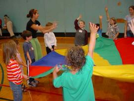 A student facilitates a cooperative parachute game with young children