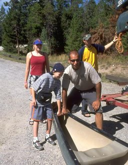 A student intern helps children with special needs prepare for a canoe trip.
