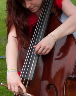 A student practices her double bass outdoors.