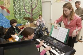 A student teacher works with a music class at a local school.