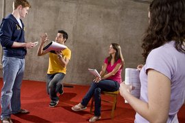A theater student directs three peers.