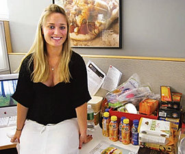 "Alexa Besgen '09 poses with food samples sent to her at ""Family Circle."""
