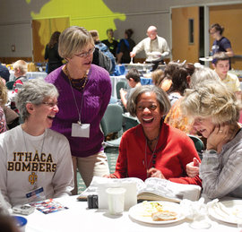 Alumnae laugh over an old yearbook at the Fall Splash picnic.
