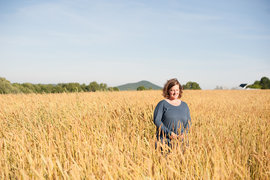 Amber Lambke in a field of grain. (Photo by Lily Piel Photography)