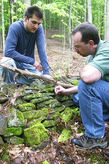 An environmental studies student performs fieldwork with his professor.