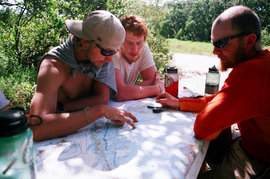 An instructor assists students with route planning while on a kayaking expedition.