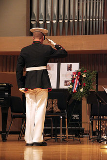 "Andrew Thomson '12 salutes in honor of a fallen comrade. Thomson's compostion ""The Letter"" premiered at the Veterans Day celebration."