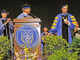 Board chair William Schwab '68 watches from podium as President  Rochon displays the Ithaca College presidential medallion