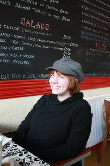 Carly sits in a cafe in Glastonbury