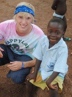 Chris Toone '13 with children in Ghana
