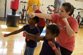 Christine Giovinazzo '11, shows Cassie and Ellie Ives, participants of IC Fit Kids, how to do punches with dumbbells. Photo by Jacob Lifschultz
