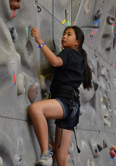 Dena Iadanza scales a rock climbing wall at HealthQuest.