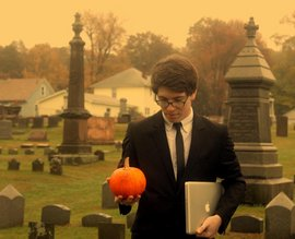 Draped in formal garb, I stand in a graveyard holding a small pumpkin in one hand and my Macbook Pro in the other. This was used as the cover art for