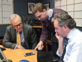 Dylan Lyons '14 (center) shows Scott Pelley (left) how to use Periscope, Twitter's live-video app. Photo by CBS Evening News